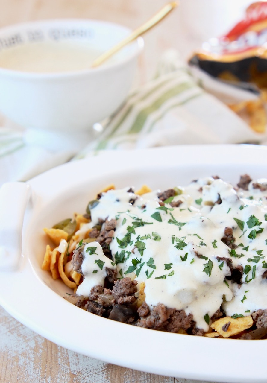 Philly Cheesesteak Frito Chili Pie in white casserole dish with Creamy Provolone Cheese Sauce and bag of Fritos