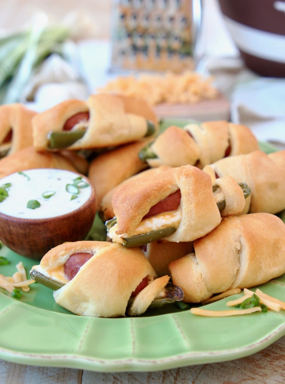 Jalapeno Poppers with a Little Smokie Sausage Wrapped in Crescent Rolls on a Green Plate with Cheddar Cheese and Ranch Dressing