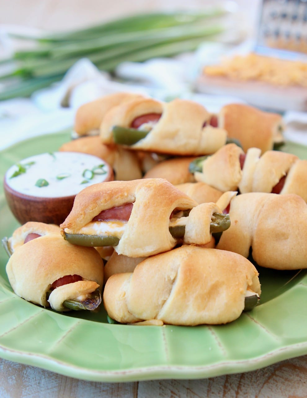 Jalapeno Popper Pigs in a Blanket on a Green Plate with Ranch Dressing