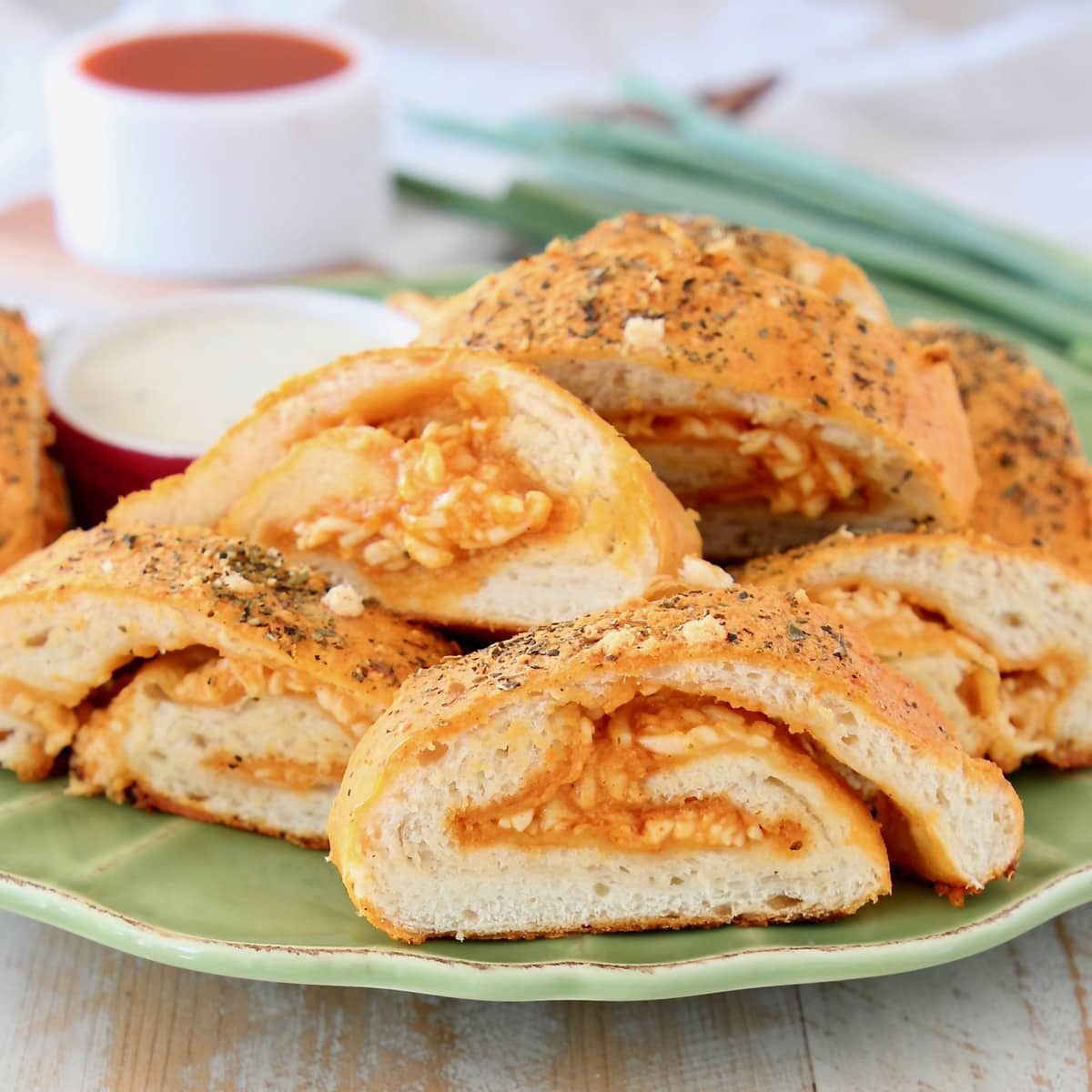 Pizza bread roll filled with buffalo sauce and cheese, sliced into pieces on a green plate with a ramekin of buffalo sauce and green onions