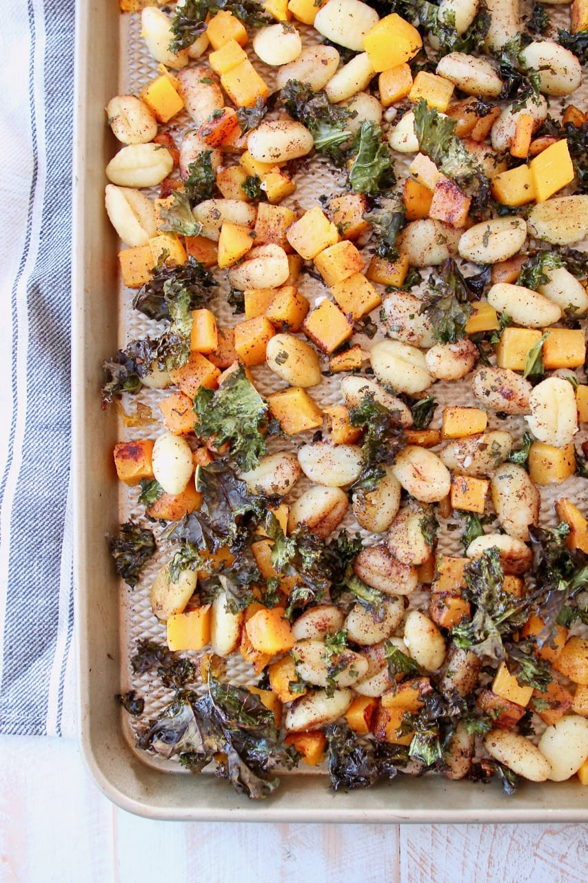 Gnocchi, butternut squash and kale on baking sheet with gray striped towel
