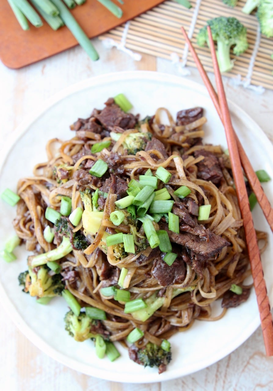 Beef and broccoli with rice noodles and scallions on plate with chopsticks