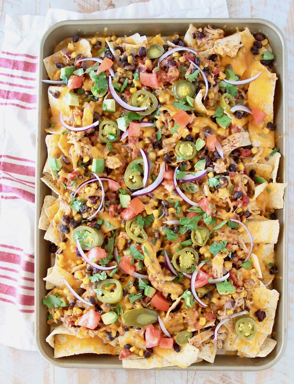 Sheet pan of chicken nachos topped with cheese, tomatoes, avocado, onions and jalapenos on red and white striped towel