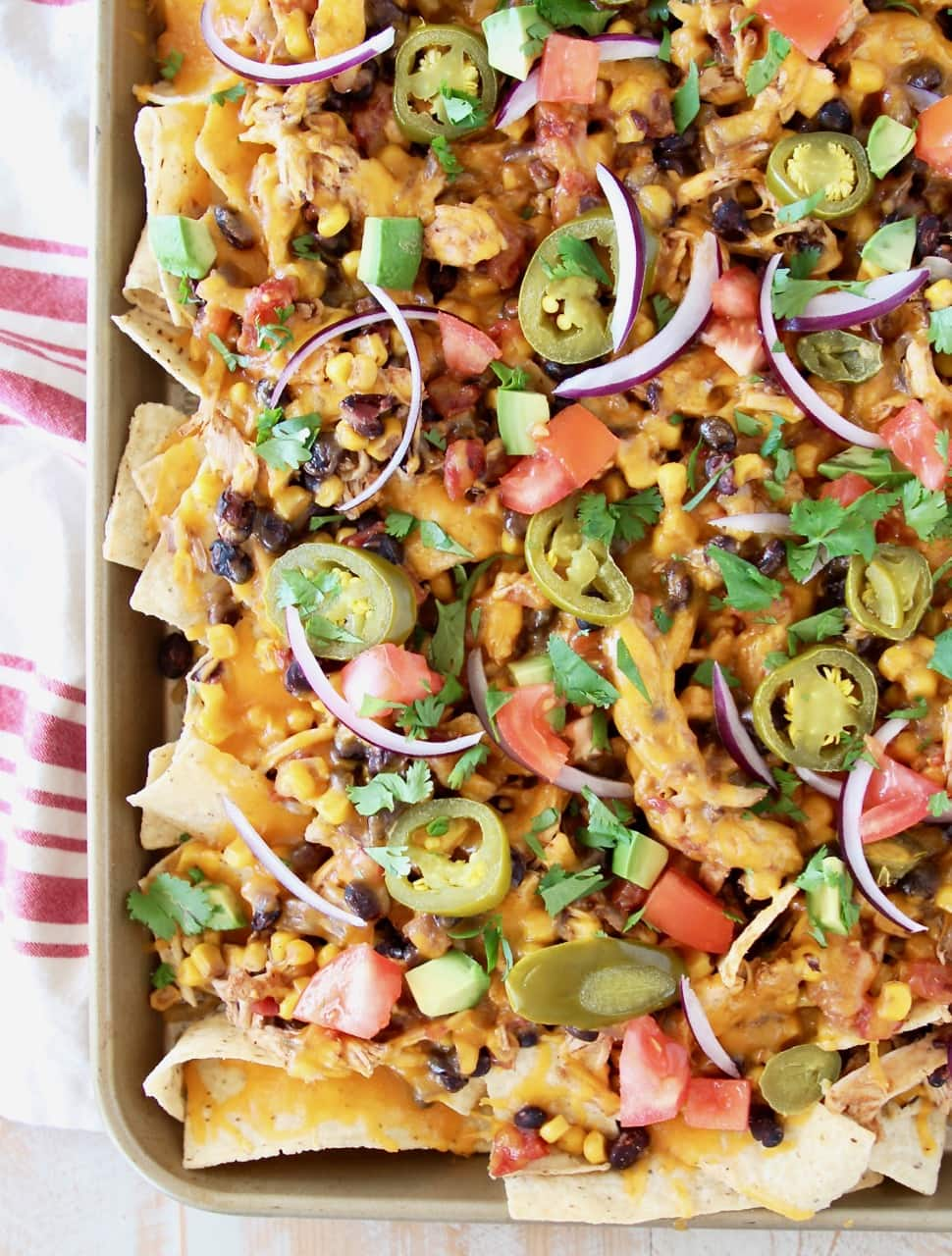 Chicken Nachos on sheet pan topped with jalapenos, red onions, tomatoes and cheese, on red and white striped towel