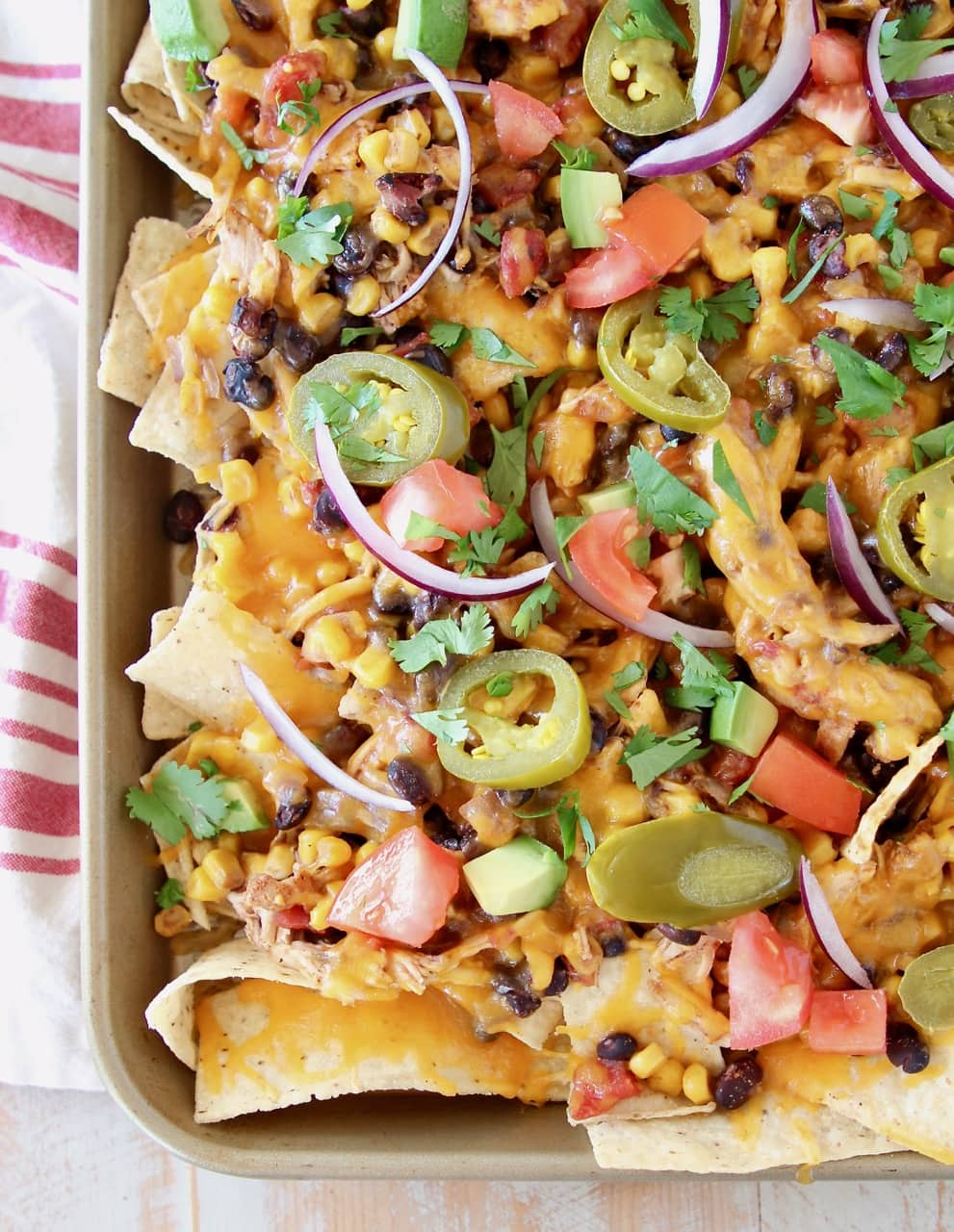 Chicken nachos on sheet pan with melted cheddar cheese, diced tomatoes, red onions and cilantro on red and white striped towel