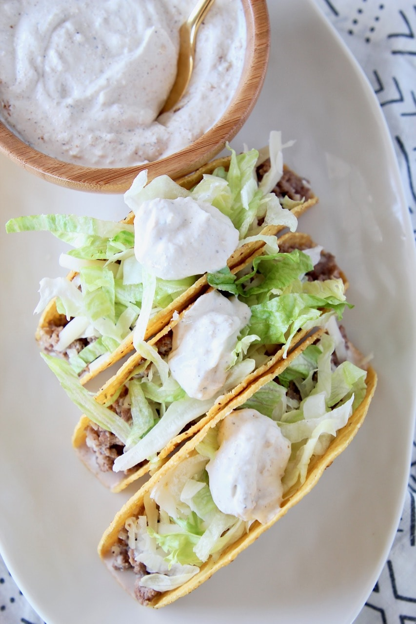 Ground beef tacos in crispy shells with shredded lettuce and french onion dip on plate with bowl of french onion dip