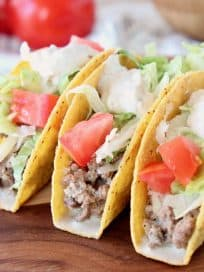 Ground beef tacos in crispy shells with diced tomatoes and shredded lettuce on wood cutting board with whole tomatoes in back