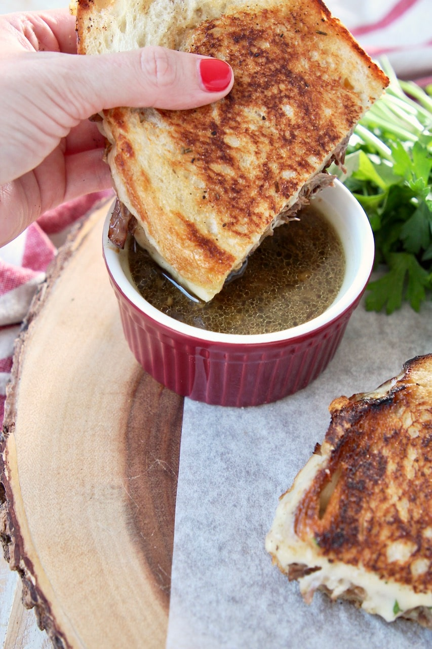 Grilled cheese pot roast sandwich held in hand, being dipped into a red ramekin of au jus