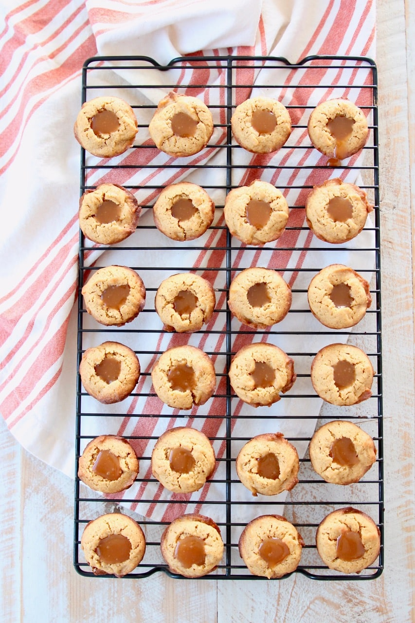 Pumpkin cookies filled with salted caramel on wire baking rack with orange striped towel
