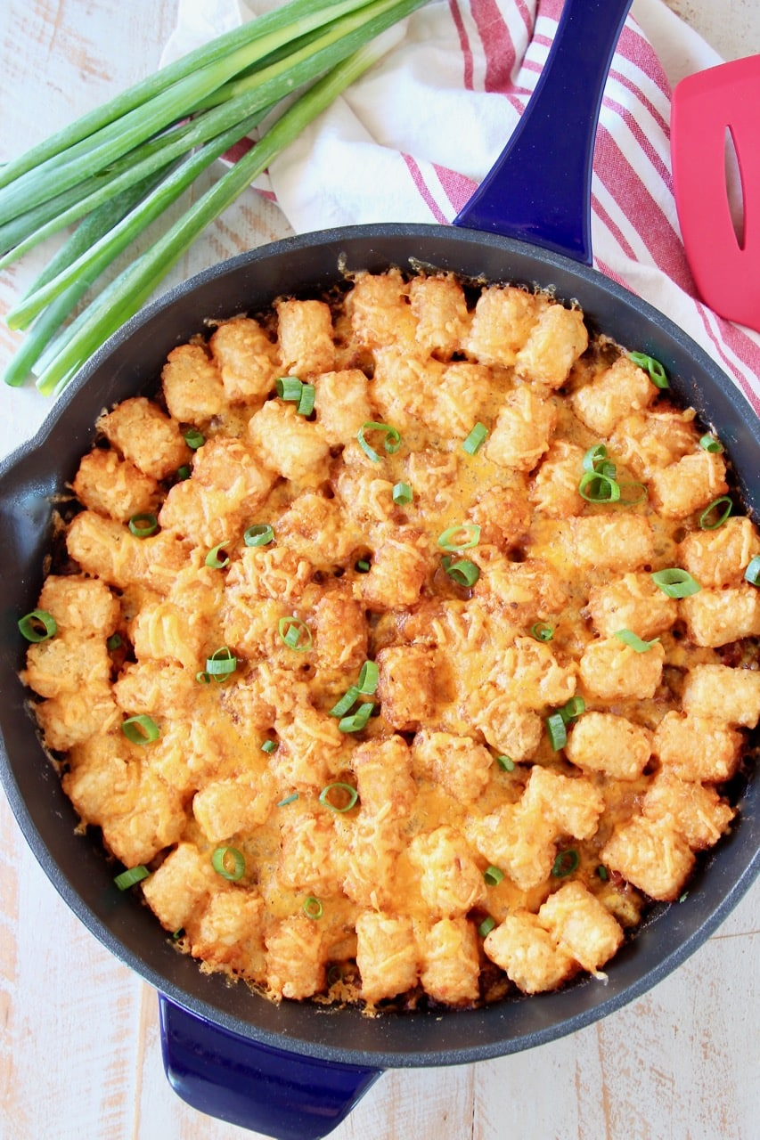The best Tater Tot Casserole with ground beef and cheese in skillet with green onions and red striped towel