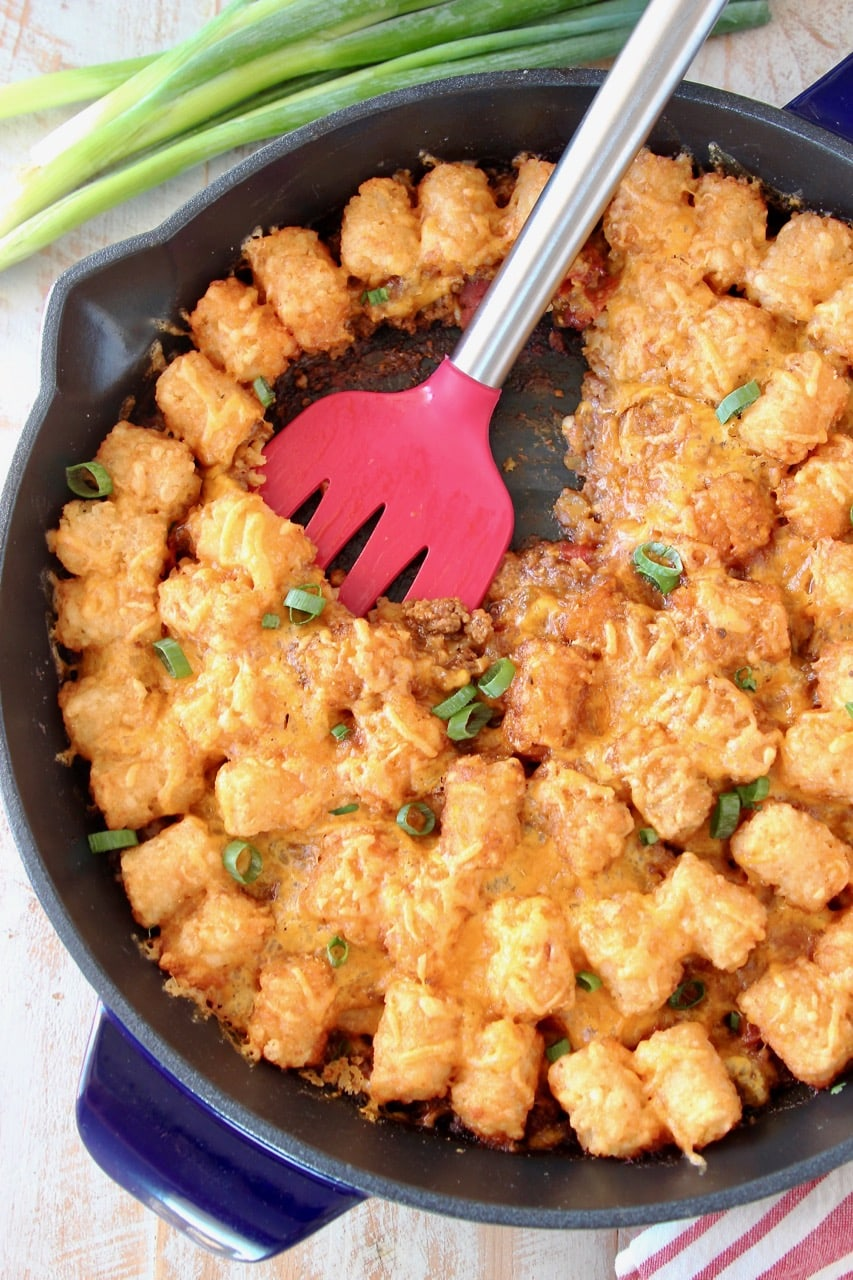 Tater Tot Casserole in cast iron skillet with red spatula and green onions
