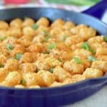 Buffalo cheeseburger tater tot casserole in skillet with green onions