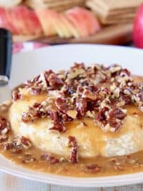 Baked brie round topped with salted caramel sauce and pecans on white plate with black cheese spreader and wooden tray of sliced apples and graham crackers in background