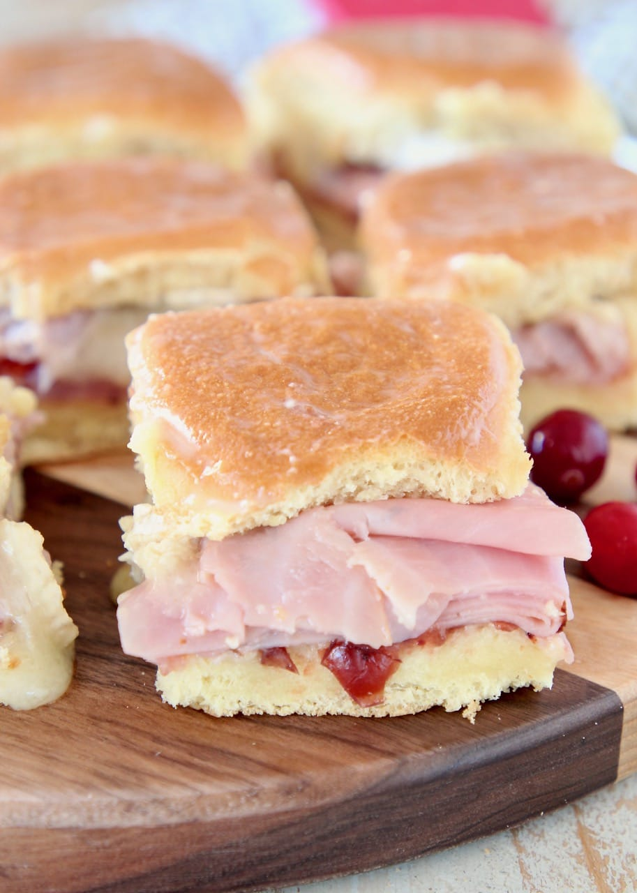 Ham Sliders on Hawaiian rolls with cranberry sauce, sitting on wood cutting board with fresh cranberries