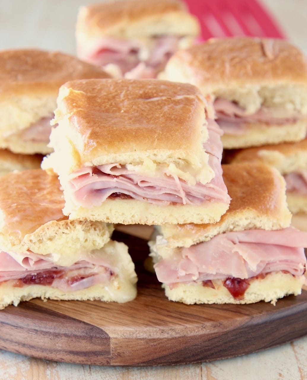 Ham sliders on Hawaiian Rolls stacked on each other on a wood cutting board