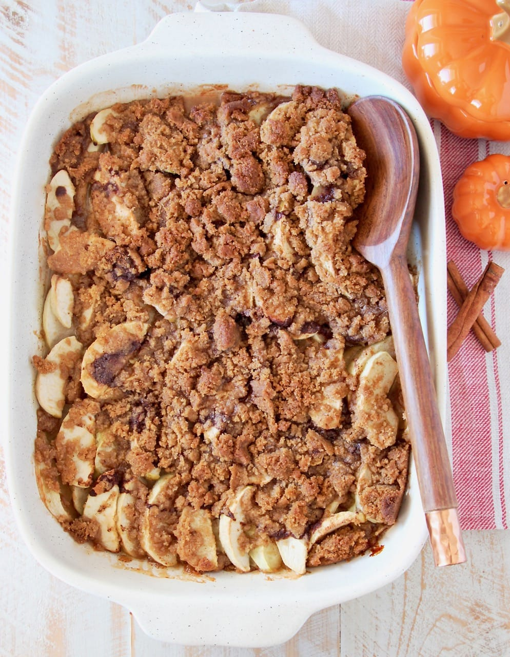 Overhead shot of apple crumble in a white casserole baking dish with a wooden spoon, sitting next to small orange pumpkins and cinnamon sticks on a red and white striped towel