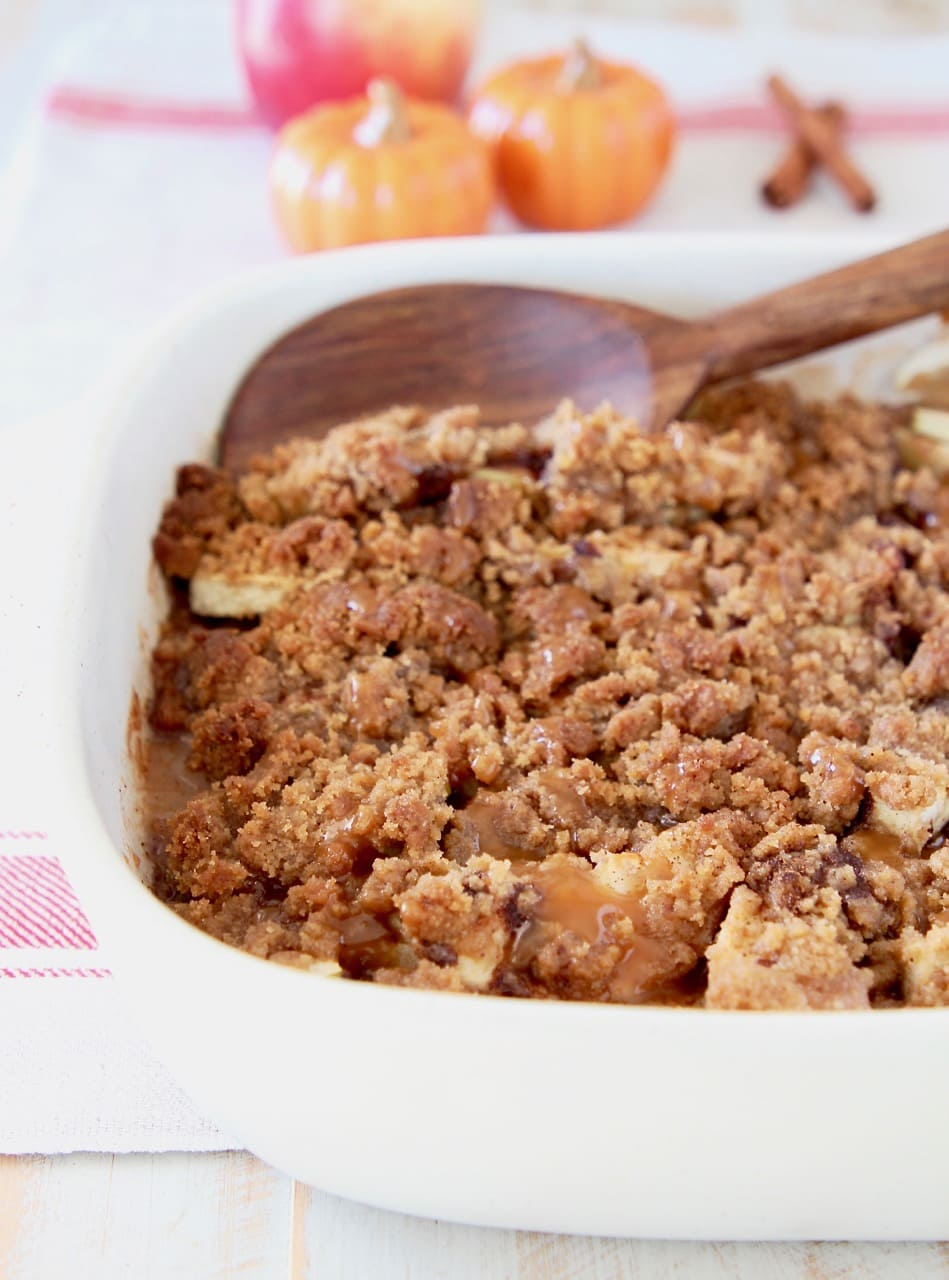 Apple crumble in baking dish with wooden spoon on white and red striped towel with small orange pumpkins in background