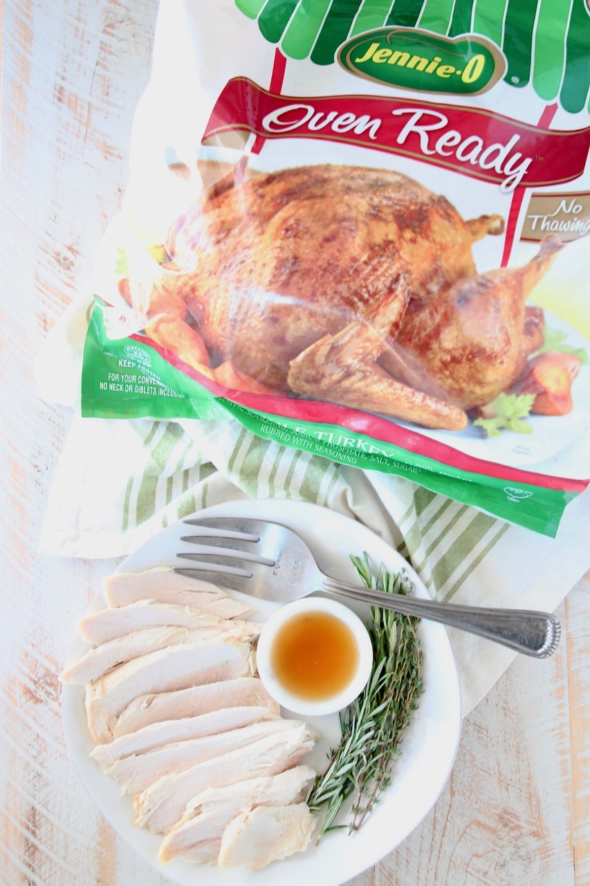 Plate of sliced roasted turkey with large fork, bowl of maple apple reduction and fresh rosemary springs, next to Jennie O Whole Oven Ready Turkey in bag