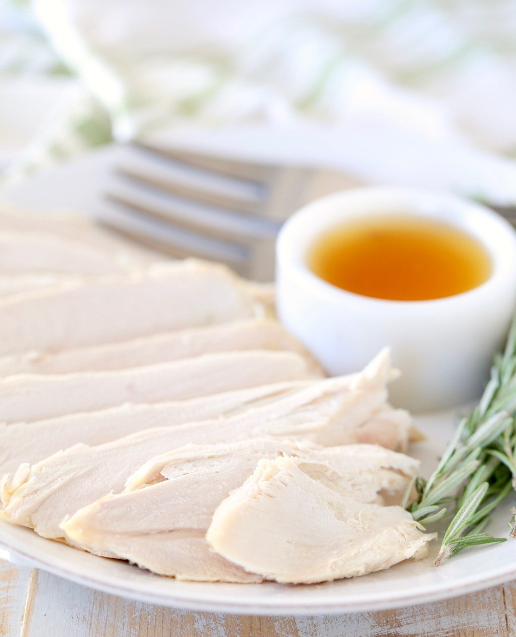 Sliced turkey breast on plate with small white ramekin of apple reduction and sprigs of fresh rosemary