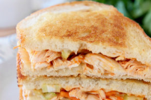Buffalo turkey grilled cheese sandwiches cut in half and stacked up on a plate