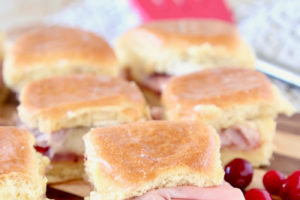 """Cranberry Brie Ham Sliders on Hawaiian Rolls - image with text overlay """"Super Easy, 4 ingredient Cranberry Brie Ham Sliders WhitneyBond.com"""""""
