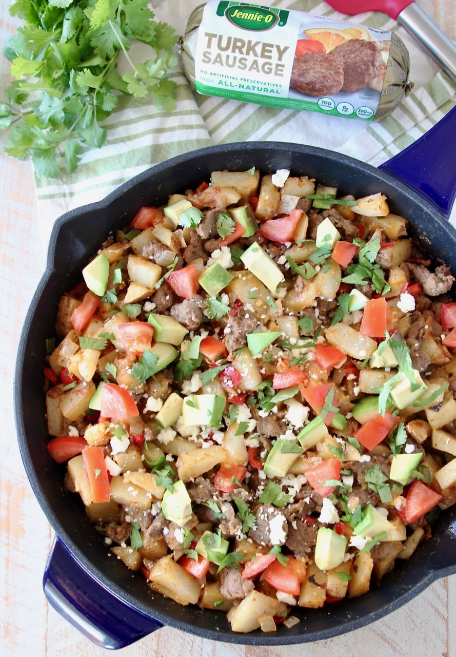 Breakfast hash in blue cast iron skillet, filled with diced potatoes, turkey sausage, avocado, tomatoes and queso fresco, with fresh cilantro and a package of Jennie-O turkey sausage