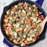 Breakfast hash in cast iron skillet with wooden spoon in pan, on top of green and white striped towel