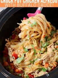 buffalo chicken fettuccine alfredo pasta being scooped out of crock pot with large spoon