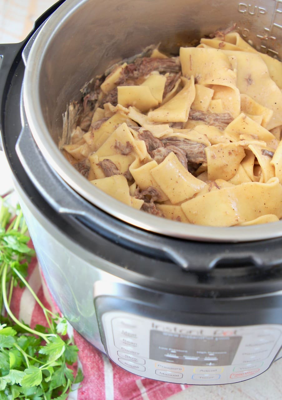 Beef stroganoff with wide egg noodles in instant pot on red and white striped towel with fresh parsley on the side
