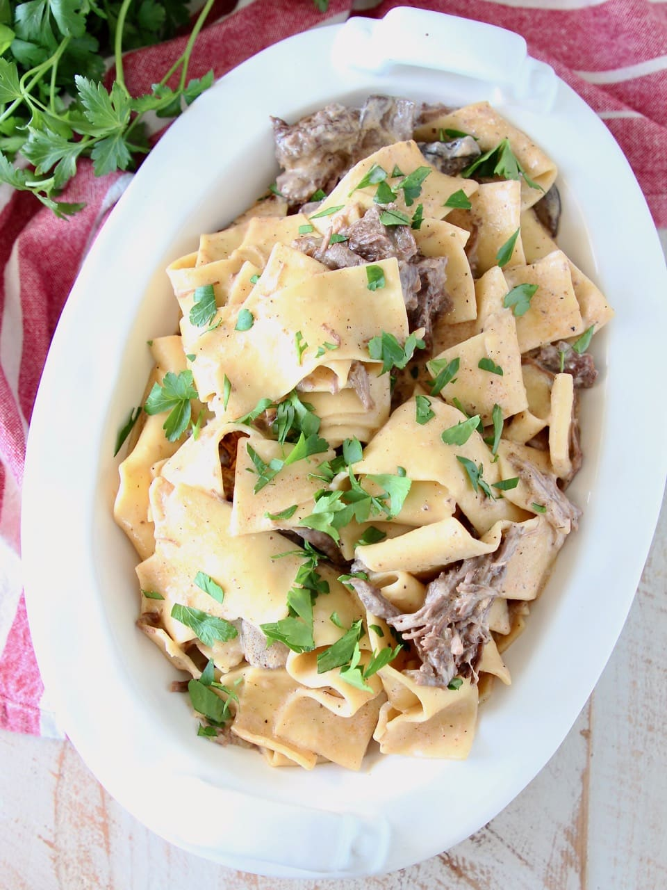Instant pot beef stroganoff in a large white oval serving dish with wide egg noodles and shredded beef, topped with fresh parsley, sitting on a red and white striped towel