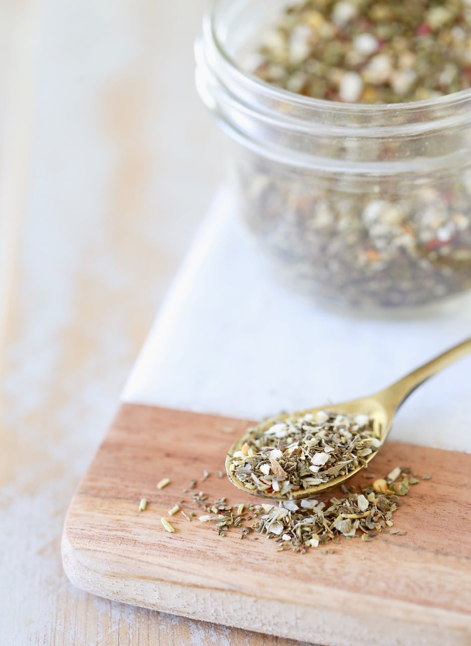 Italian seasoning in small mason jar on wood and marble cutting board with a small gold spoon of Italian seasoning in front of the mason jar