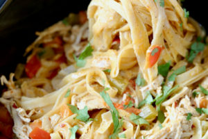 Buffalo chicken alfredo with fettuccine noodles in crock pot with text overlay