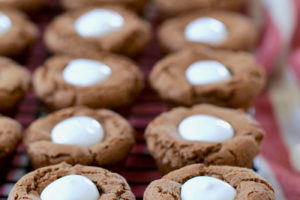 Chocolate cookies formed into cups filled with marshmallow creme on black wire baking rack