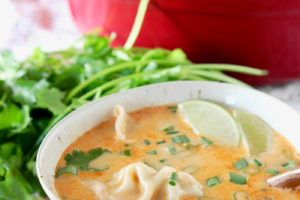 Potsticker soup in bowl with lime wedges and fresh cilantro