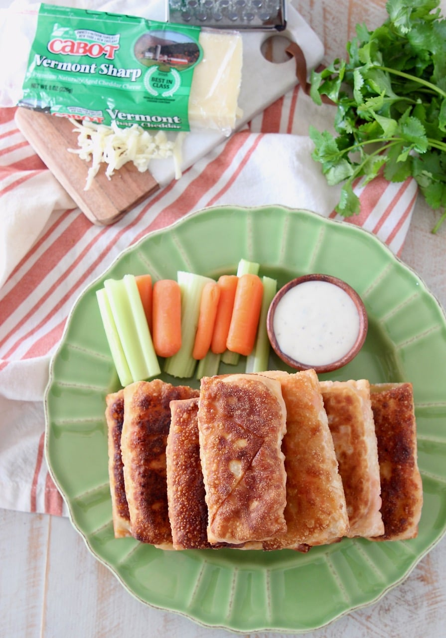 Overhead shot of buffalo chicken egg rolls stacked on top of each other on a green plate with carrot and celery sticks and a wood ramekin of ranch dressing
