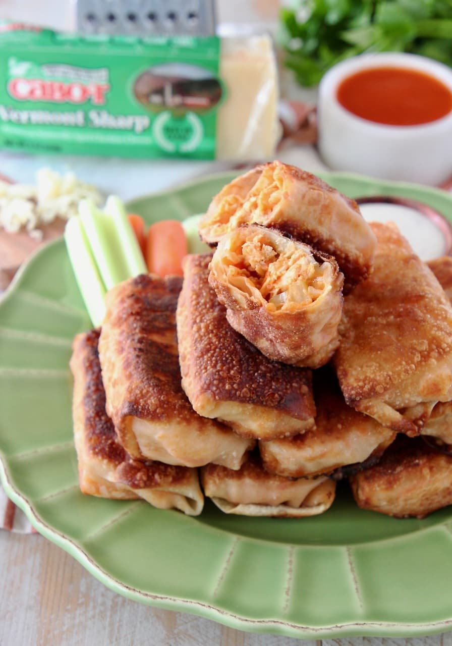 Buffalo chicken egg rolls stacked on each other on a green plate with the top egg roll cut in half