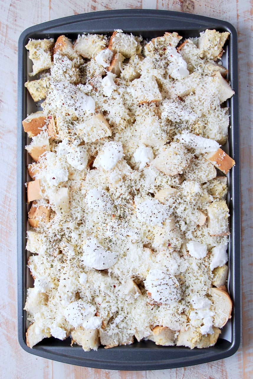 Garlic bread covered in cheese on a baking sheet