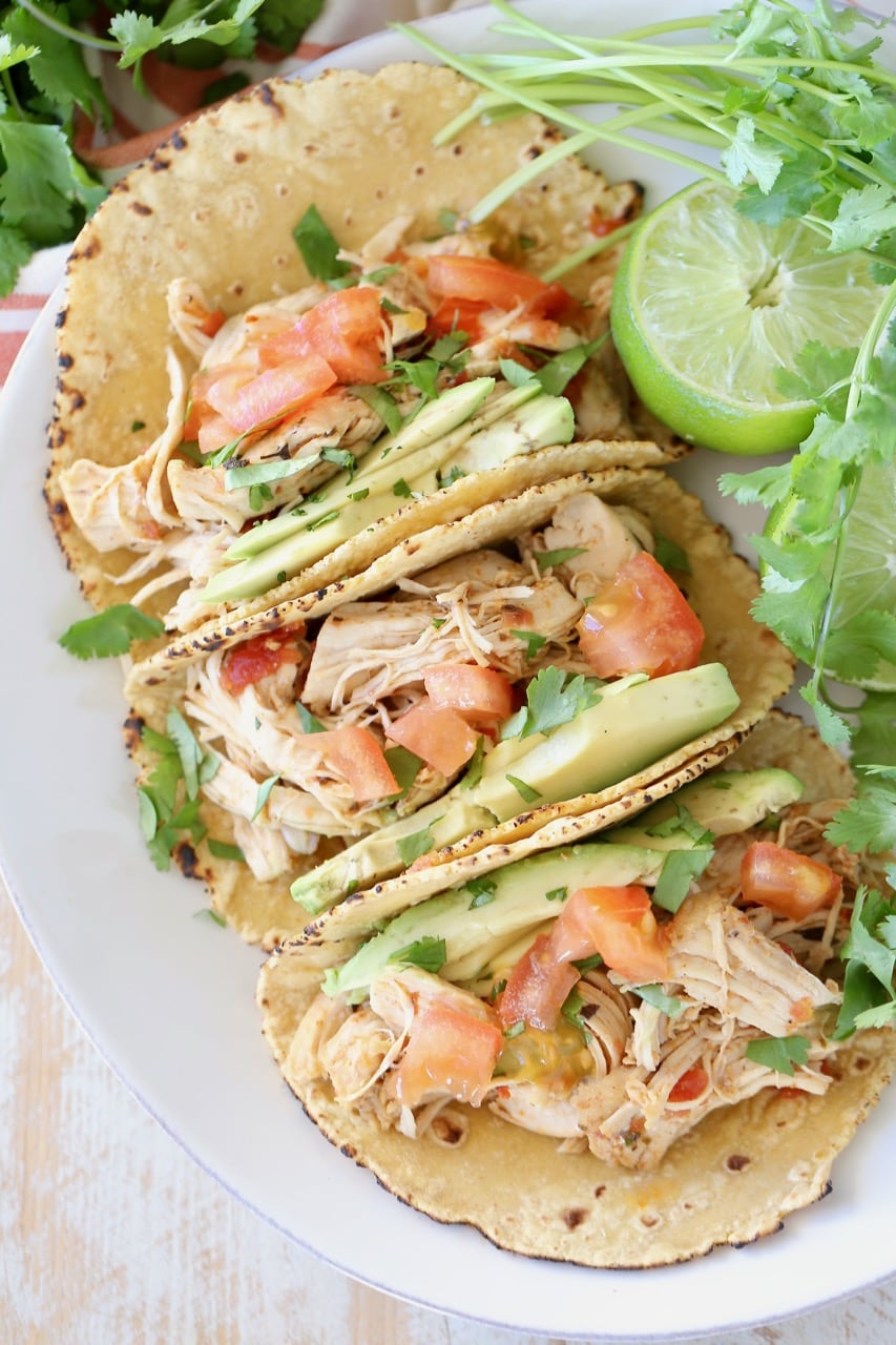 Shredded pressure cooker chicken tacos in corn tortillas on white plate with cilantro and lime