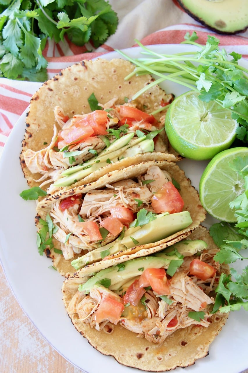 Overhead shot of shredded chicken tacos in corn tortillas on white plate with cilantro and limes