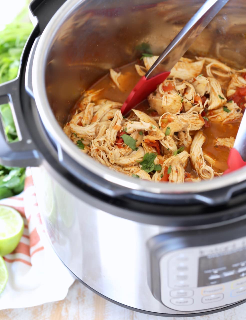 Shredded taco chicken in Instant Pot with red tongs and cilantro