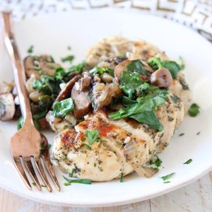 White plate of sliced spinach mushroom chicken with copper fork on the side of the plate, sitting on a gold and white patterned napkin
