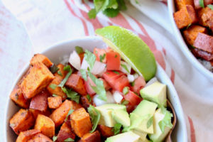 """Sweet potatoes, avocado, pico de gallo and lime wedge in bowl, image with text overlay """"Mexican Sweet Potato Quinoa Bowls, easy, vegan, gluten free"""""""