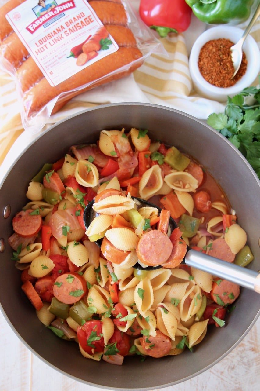 Cajun pasta with sausage and peppers in pot with spoon and package of sausage on the side