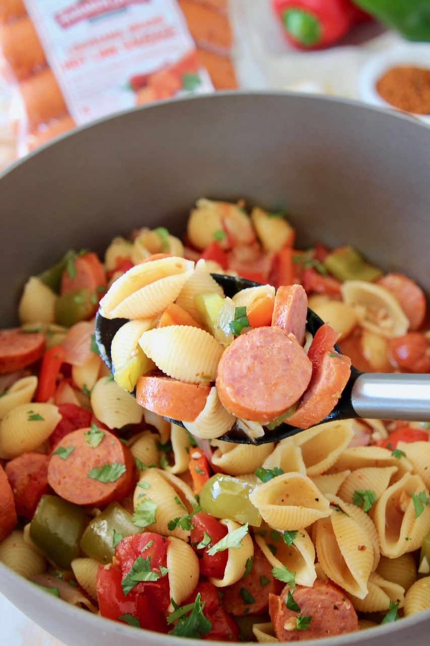 Cajun sausage and pasta in spoon, coming out of a pot