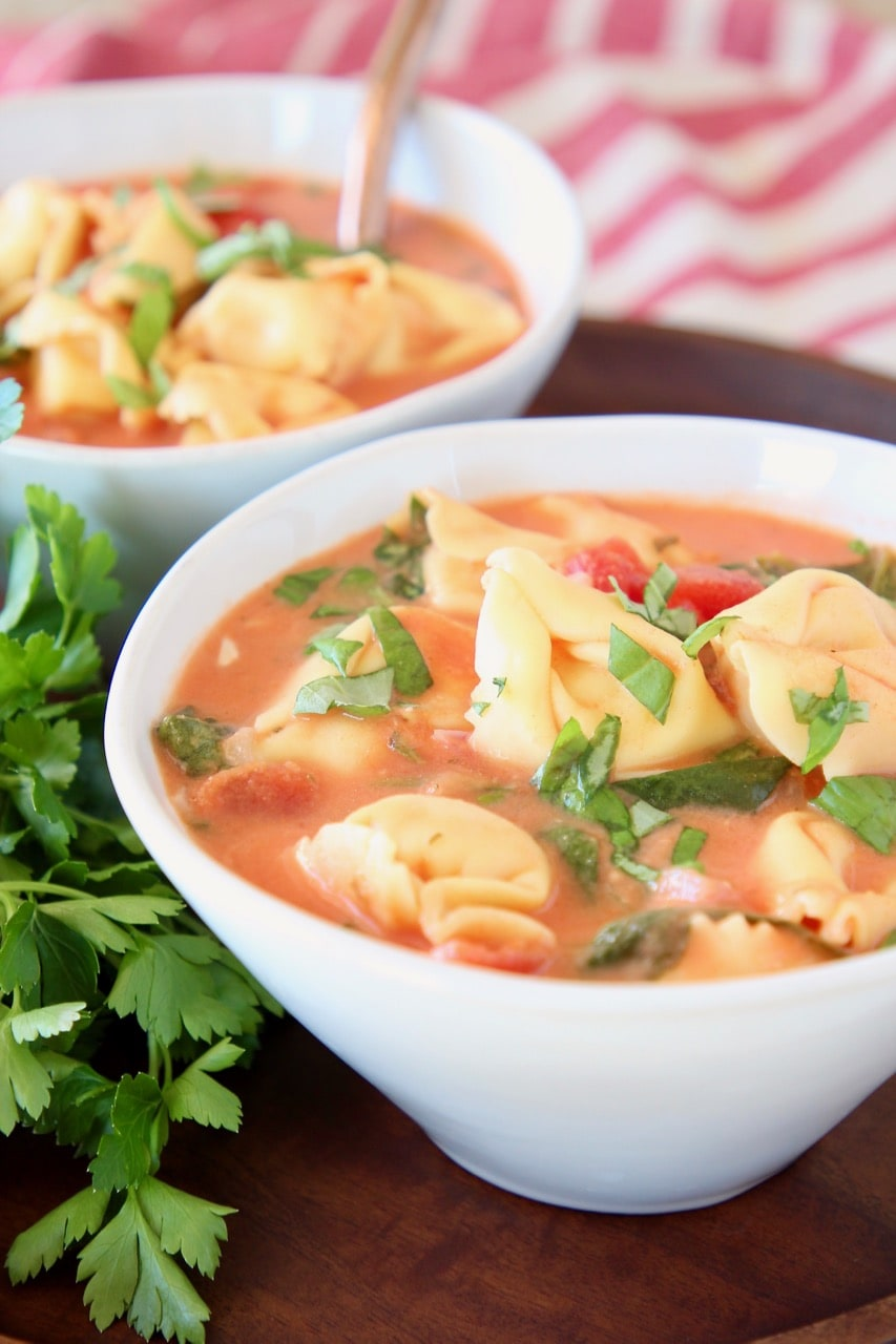 Creamy tomato tortellini soup in white bowl with fresh parsley and diced tomatoes