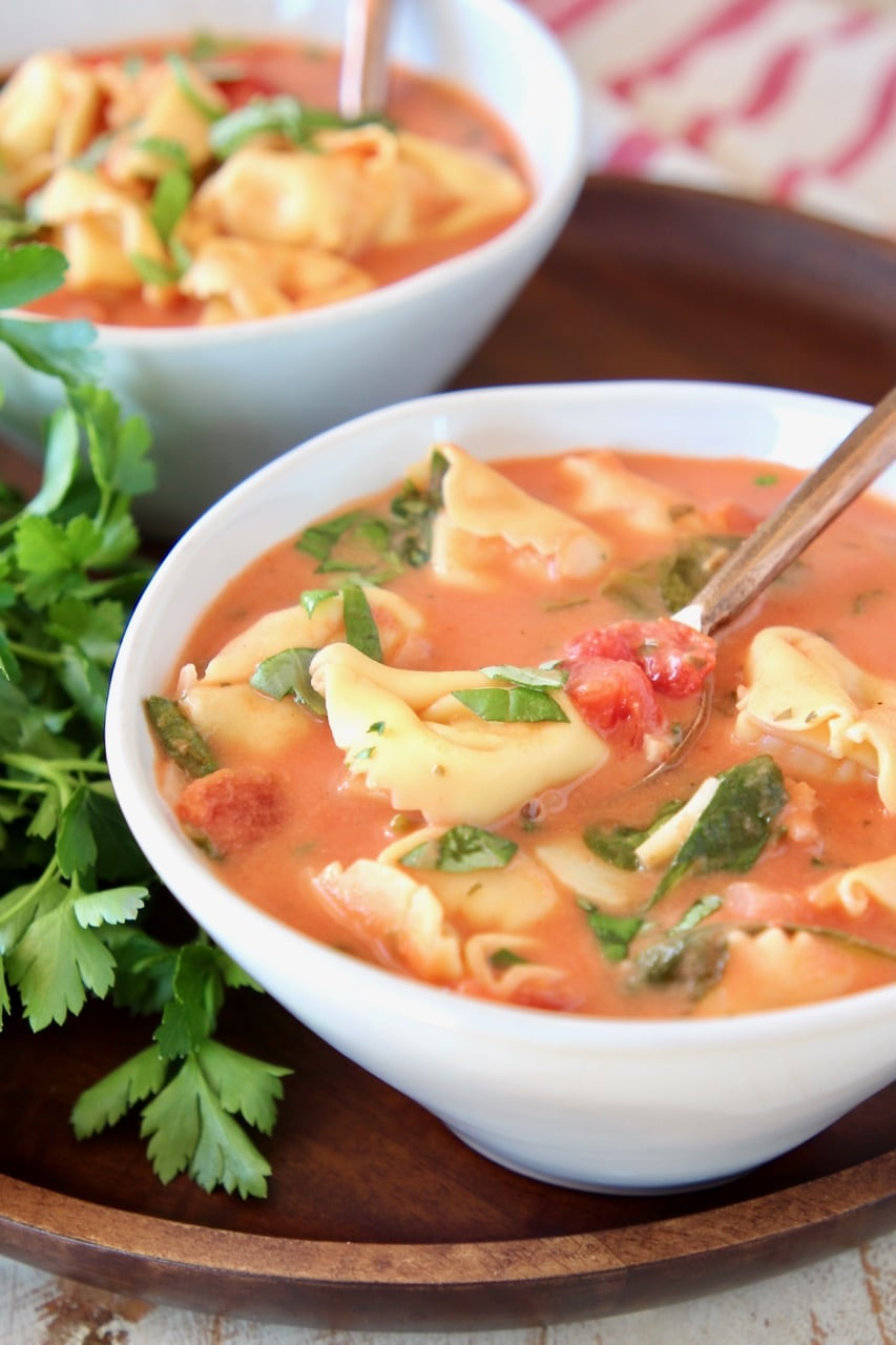 Tomato basil tortellini soup in bowl with copper spoon and fresh parsley on the side