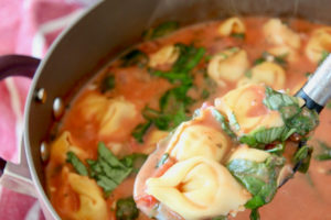 Pot of tortellini soup with spoonful of soup scooped out of the pot