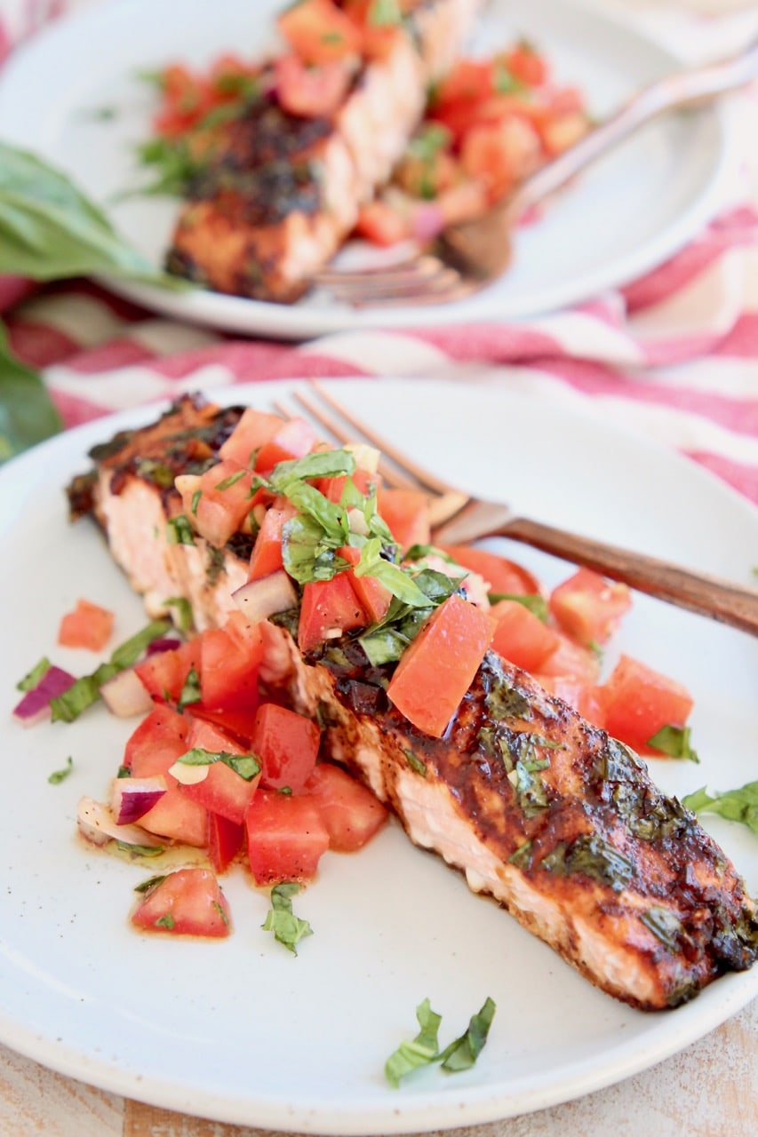 Balsamic glazed piece of salmon on plate topped with tomato basil bruschetta