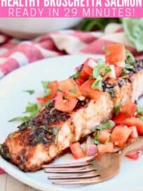 Slice of baked salmon on plate with tomato bruschetta topping