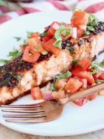 Piece of bruschetta salmon on plate with copper fork